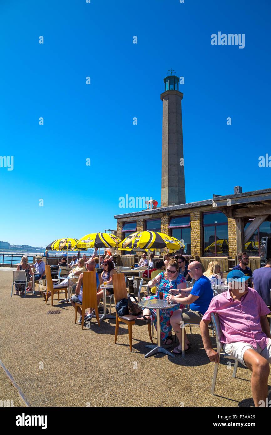 People sitting at cafe tables on a hot summer day at the Harbour Arm in Margate, UK - Stock Image