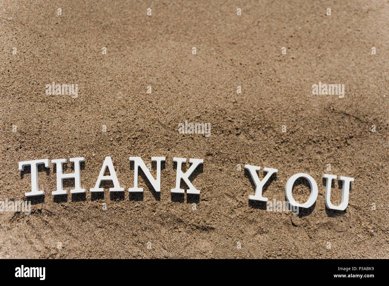 thank you word drawn on the beach sand - Stock Image