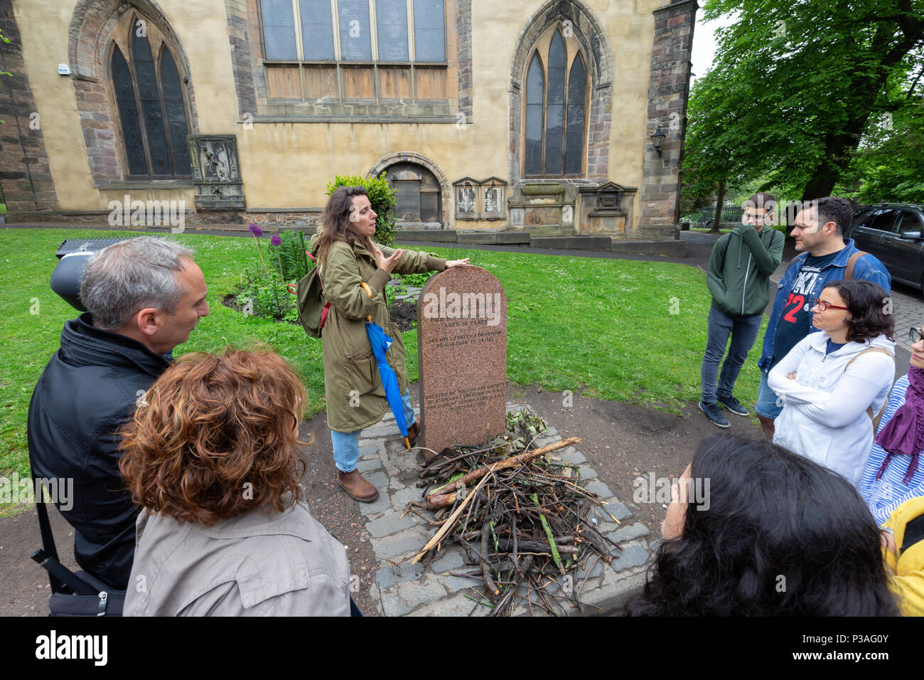 Tourists on a guided tour of edinburgh visiting the grave of Greyfriars Bobby dog, Greyfriars Kirk, Edinburgh Old Town, Edinburgh Scotland UK - Stock Image