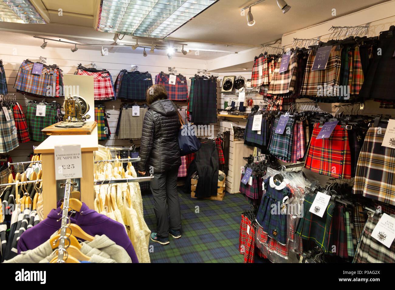 A woman shopping for kilts , in a kilt shop, Edinburgh, Scotland UK - Stock Image