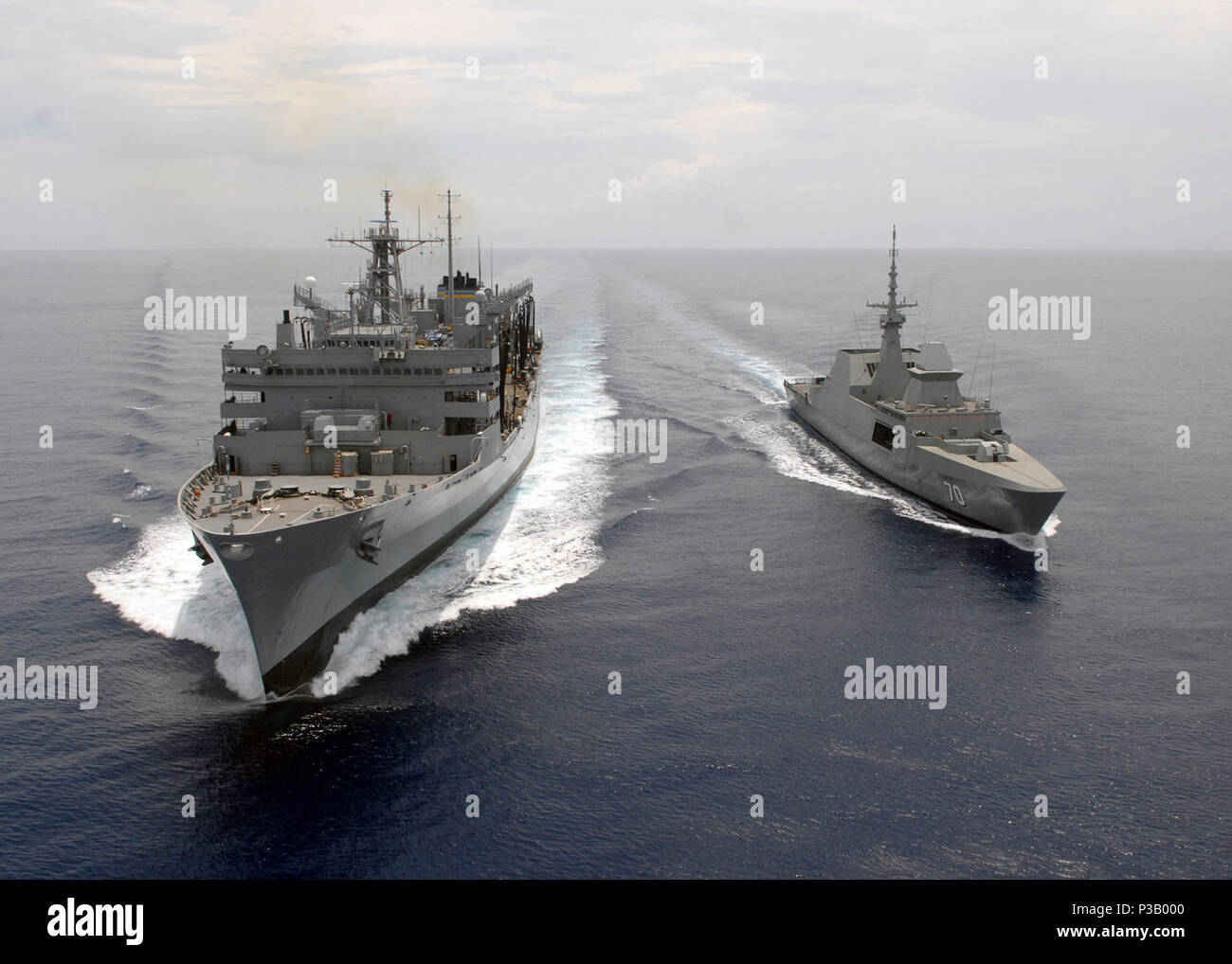 OCEAN (April 15, 2008) The Republic of Singapore Navy guided-missile frigate RSS Steadfast (FFG 70) comes alongside the Military Sealift Command fast combat support ship USNS Rainer (T-AOE 7) during a simulated refueling at sea. Rainer and other ships assigned to Carrier Strike Group 9 are on a scheduled seven-month deployment to the U.S. 5th Fleet area of responsibility.  U.S. Navy - Stock Image