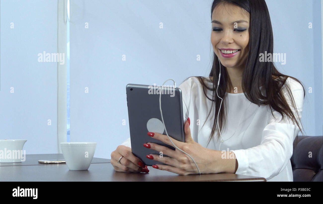 Smiling woman in earphones having video call via digital tablet in a cafe - Stock Image