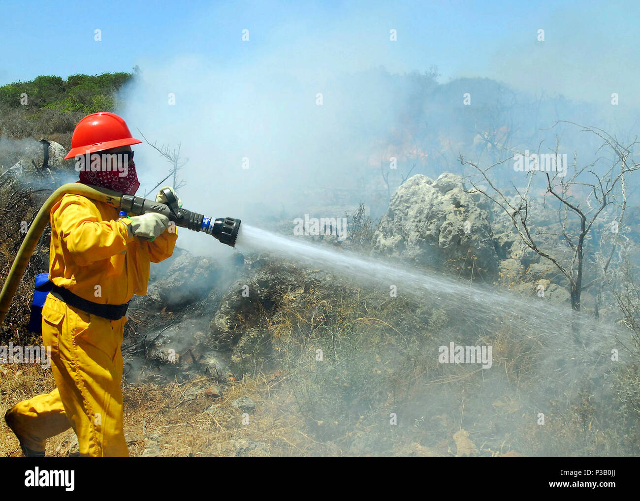 Crete, Greece (July 23, 2008) Georgios Sgouromalis, a Navy civilian firefighter, fights a brush fire near the Chania International Airport. Naval Support Activity (NSA) Souda Bay responded to a request for assistance from local authorities and dispatched 21 firefighters and five emergency vehicles to the scene, along with two Seabees and other personnel for ground support and liaison. Stock Photo