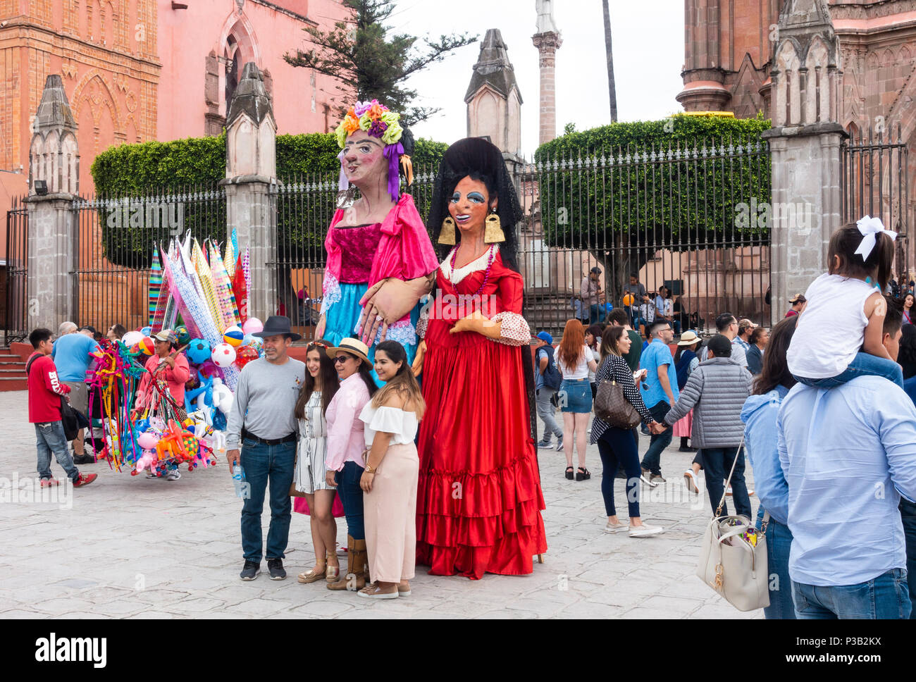 Family of four having their picture taken with two mojigangas in front of Parroquia de San Miguel Arcangel Catholic Church - Stock Image