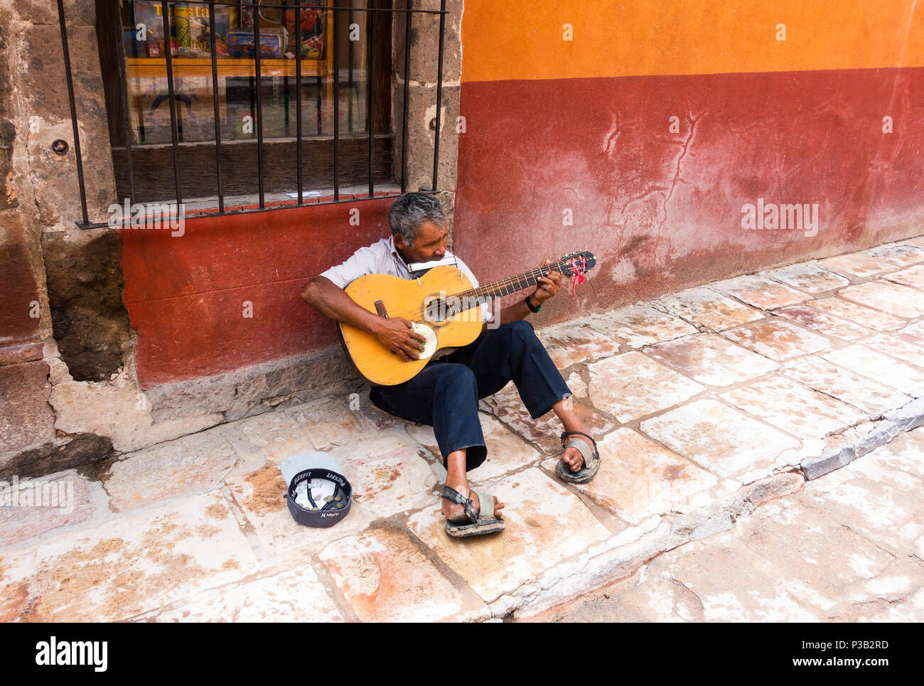 Crippled busker playing guitar and harmonica, collecting money in a hat, in San Miguel de Allende - Stock Image