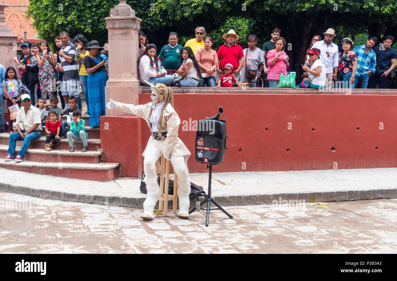 Costumed entertainer being watched by people in La Jardin in the center of San Miguel de Allende - Stock Image