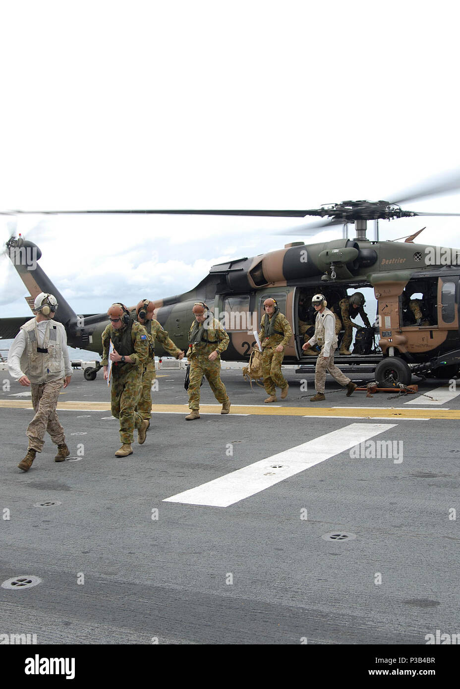 U.S. Marine Corps Lance Cpls. Tanner Foster and Brian Gill, both in white, escort Royal Australian Army pilots out of an S-70 Black Hawk helicopter aboard the forward-deployed amphibious assault ship USS Essex (LHD 2) July 8, 2009, while under way in the Coral Sea. The pilots are touring the ship before the scheduled Talisman Sabre 2009, a biennial, joint, combined exercise sponsored by U.S. Pacific Command and the Australian Defense Force that focuses on the planning and execution of contingency response operations. (DoD Stock Photo