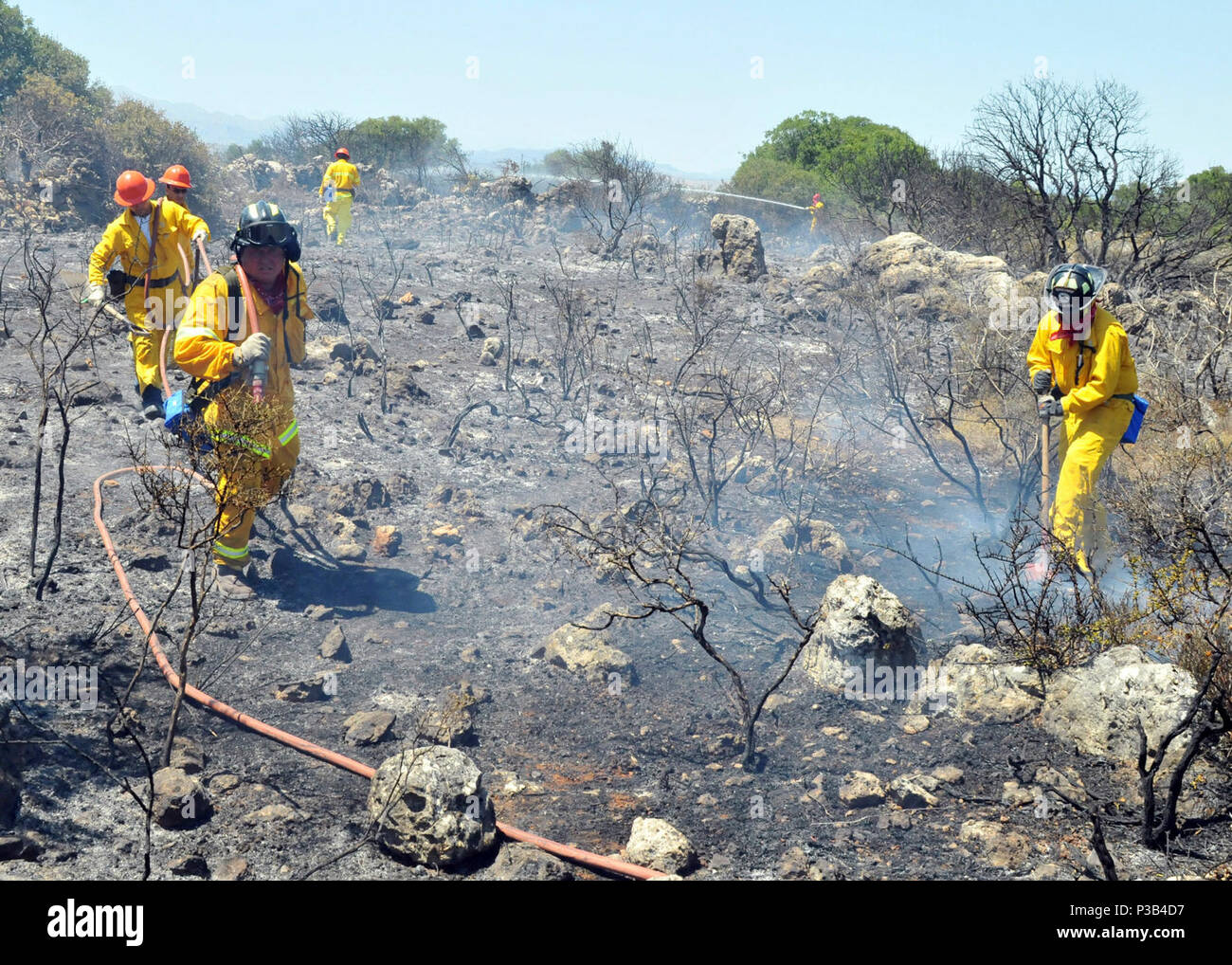 firefighters from Naval Support Activity Souda Bay extinguish the remnants of a brush fire near the village of Pazinos in western Crete, Greece, July 11, 2009. The firefighters are responding to a request for assistance from local agencies. Stock Photo