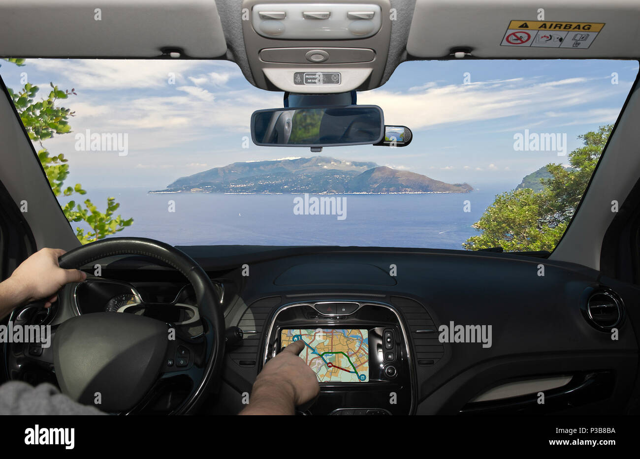 Driving a car while using the touch screen of a GPS navigation system towards Sorrento Peninsula, as seen from Capri, Bay of Naples, Italy - Stock Image