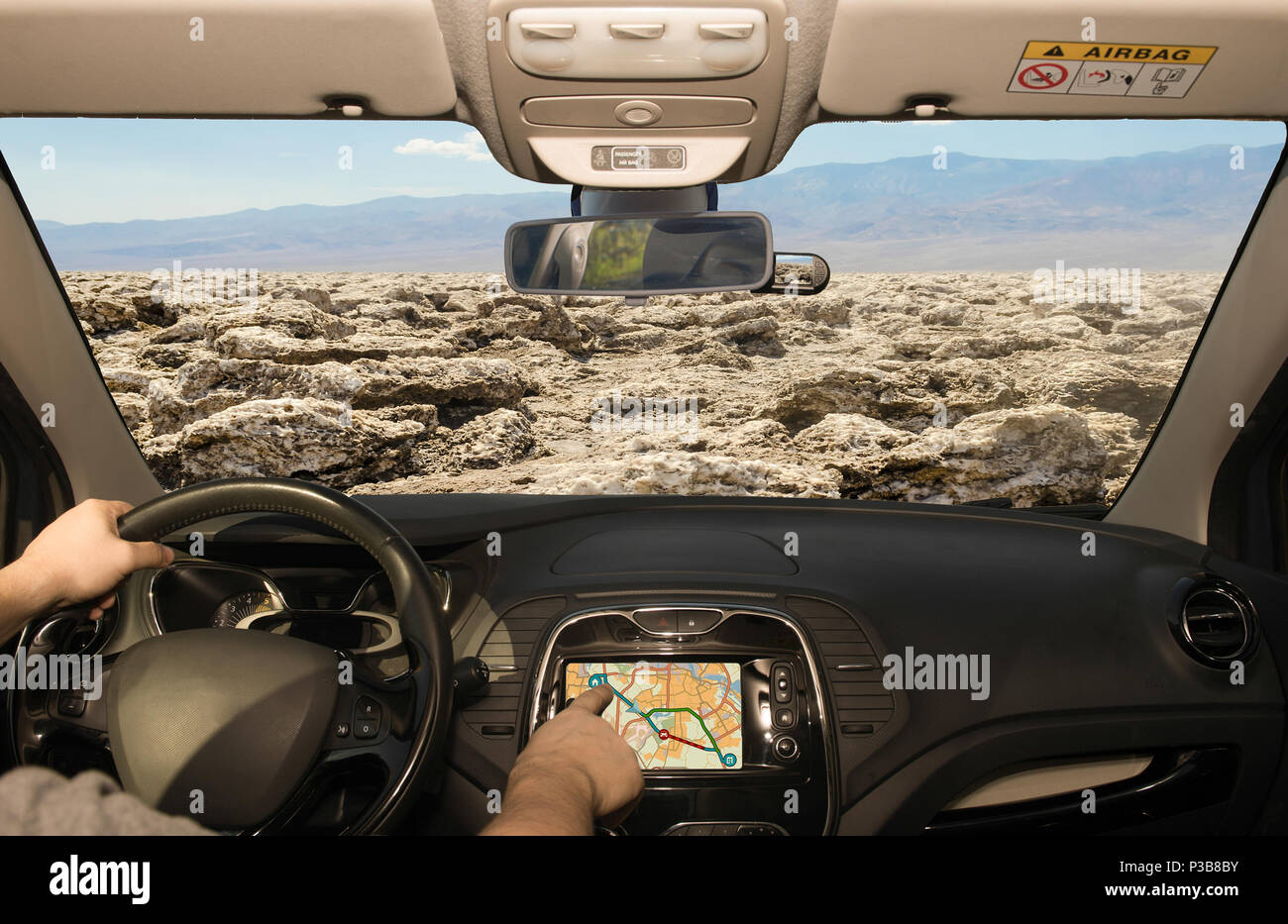 Driving a car while using the touch screen of a GPS navigation system towards Devil's Golf Course, Death Valley, USA - Stock Image