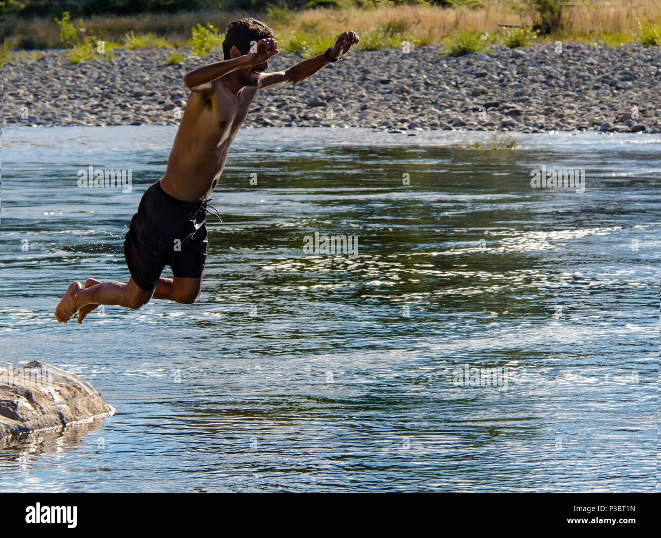 Indian man jumps into the Motueka river in New Zealand - Stock Image