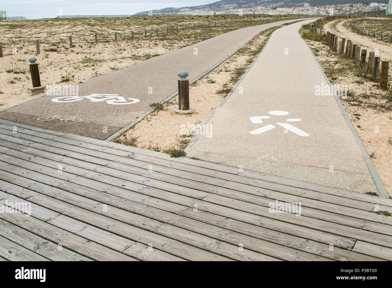 Parallel paths on a beach marked for pedestrians and bicyclists. - Stock Image