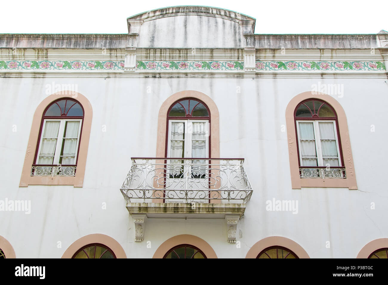 Exterior white wall of a building with arched windows with pale ...