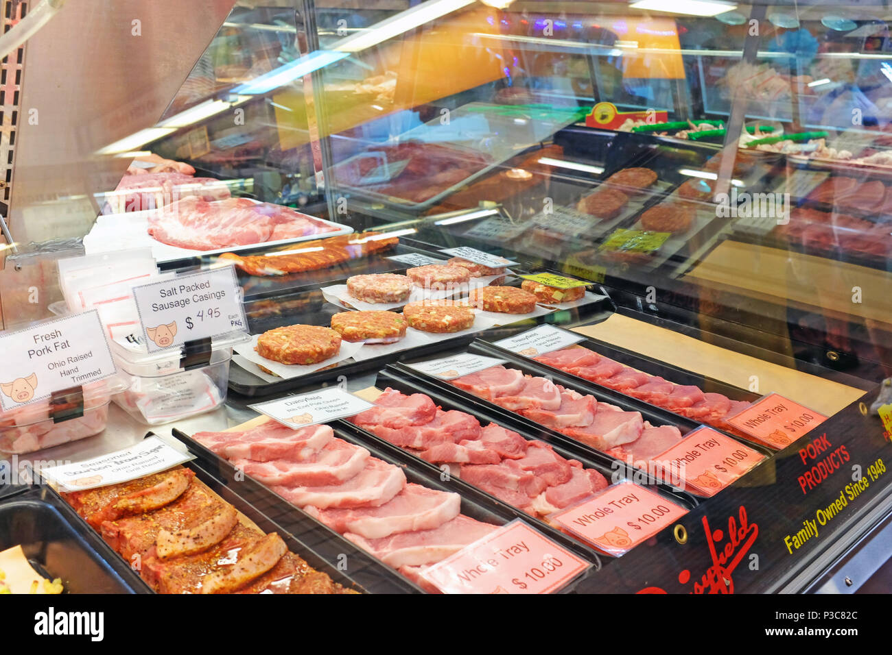 Fresh pork and various meat priced for sale in a case in the Westside Market in Cleveland, Ohio, USA in June 2018 - Stock Image