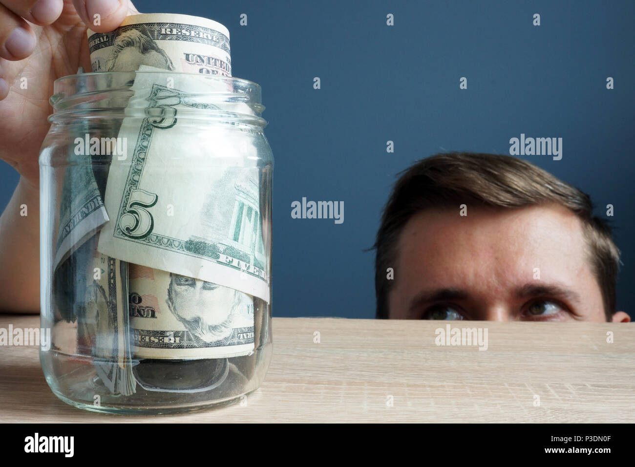 Man takes out the banknote from the jar. Financial infidelity concept. - Stock Image