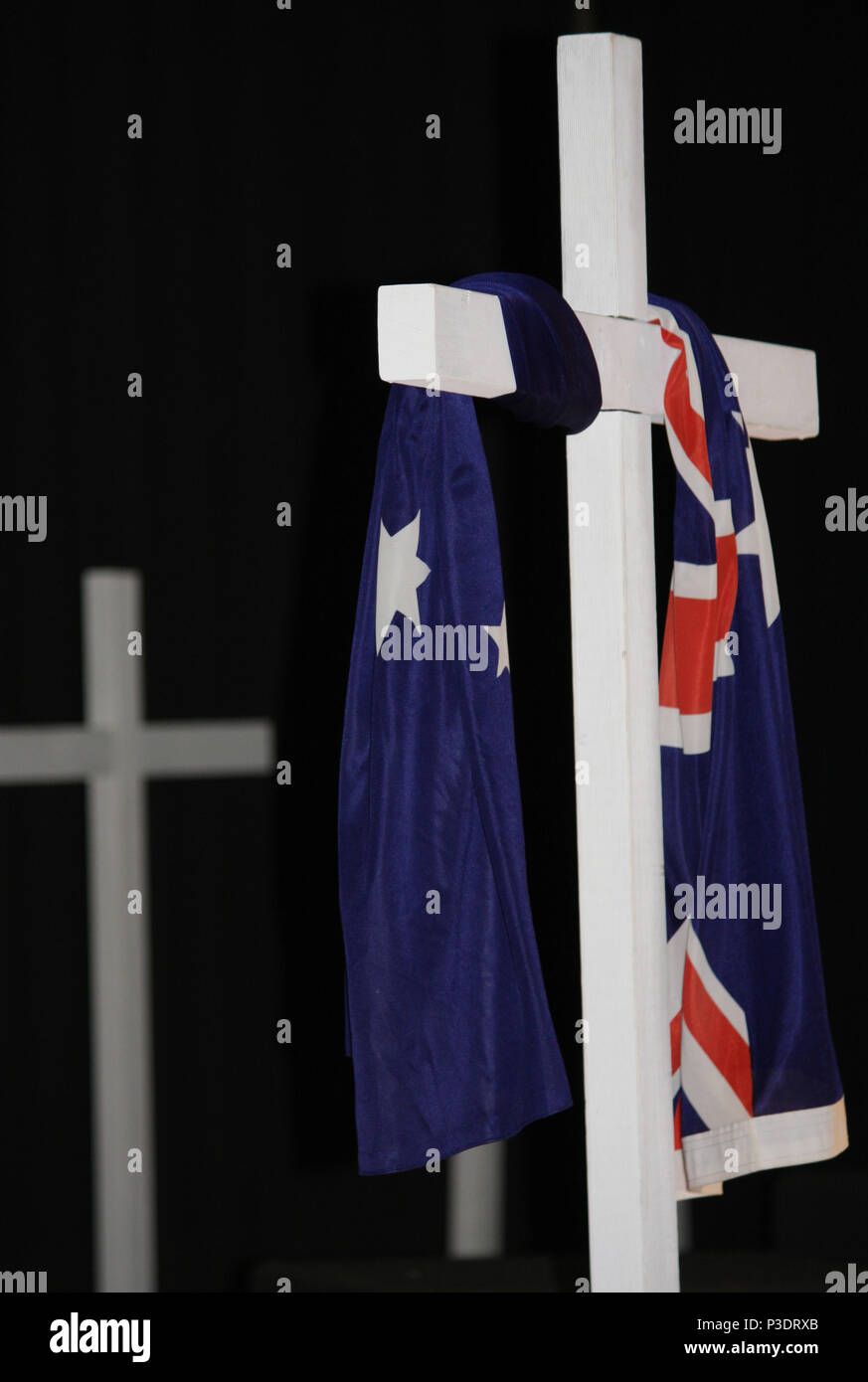 The Australian Flag symbolically draped over a white cross with dark background. - Stock Image