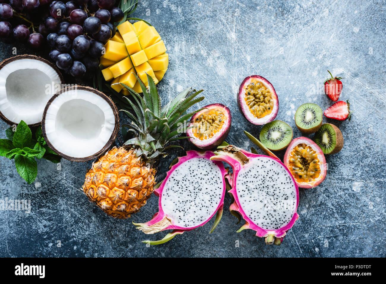 Group of exotic tropical fruits. Mango, dragon fruit, passion fruit, coconut, kiwi, pineapple and strawberry on concrete blue background. Fresh fruit  - Stock Image