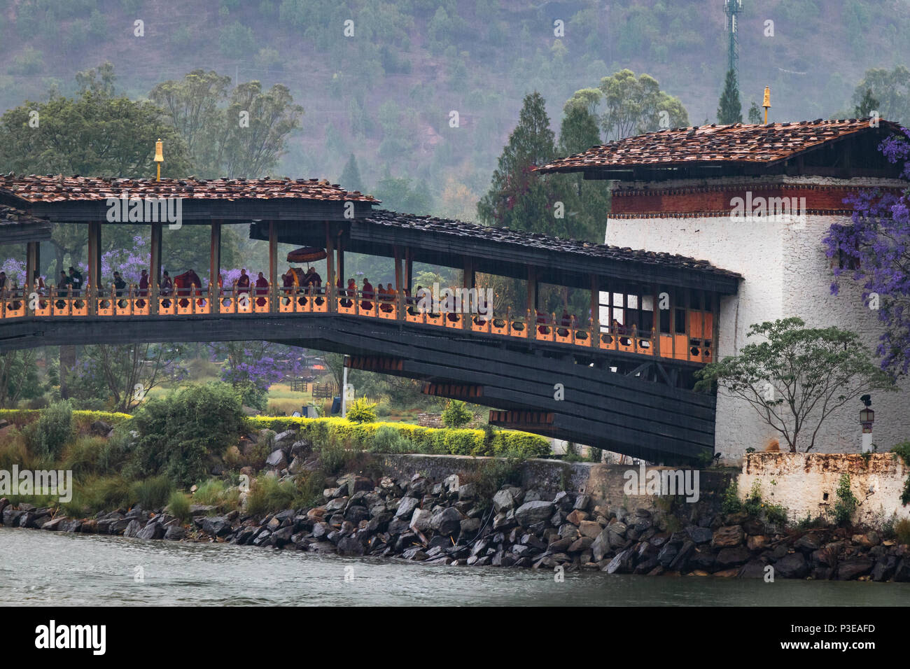 The wooden bridge at the entrance of Punakha Dzong with a lot of Monks walking on it during a religious procession - Stock Image