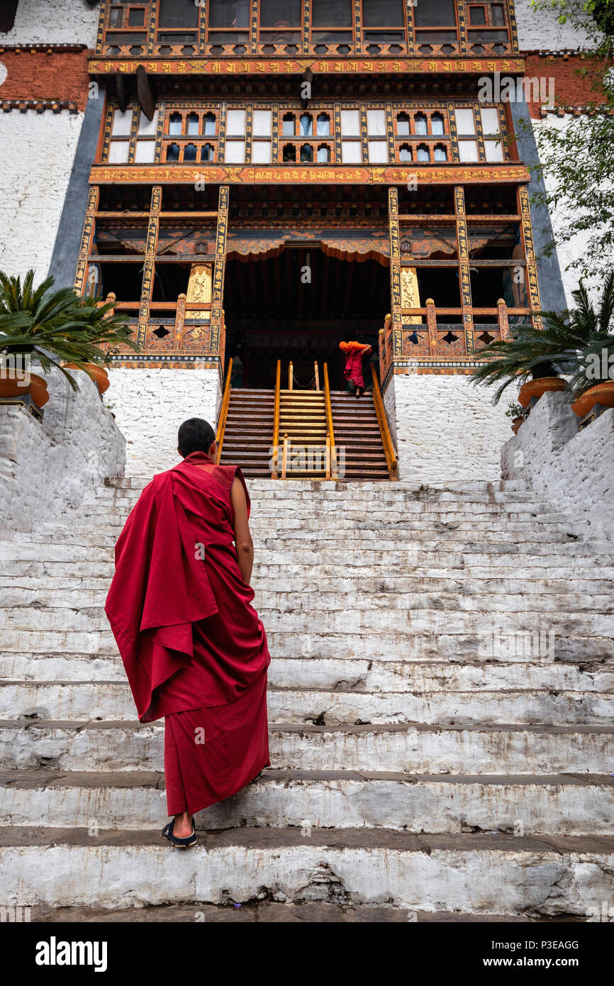The beauty of Punakha Dzong is incomplete without its monks, drapped in red robe. Stock Photo
