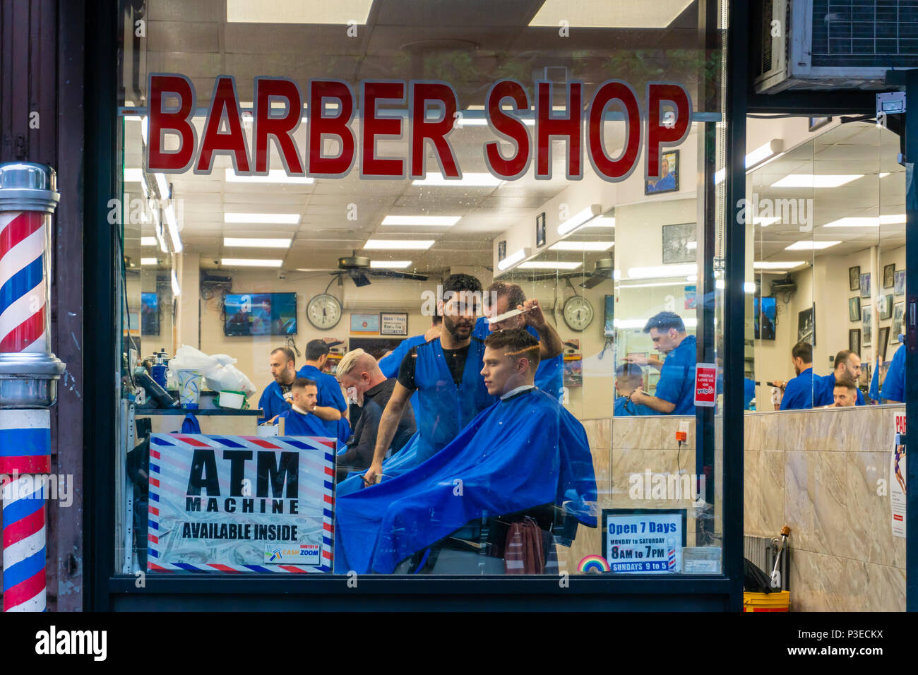 People getting haircut in a barber shop - Stock Image