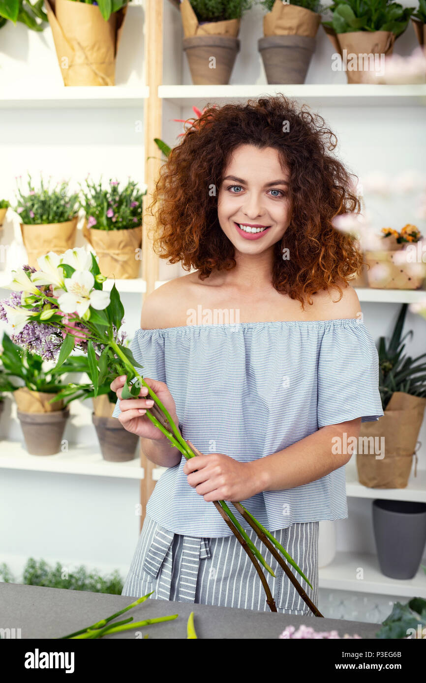 Delighted nice woman holding flowers - Stock Image
