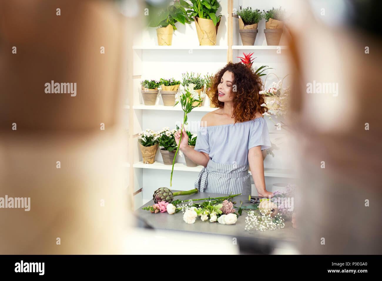 Joyful charming woman standing at the table - Stock Image