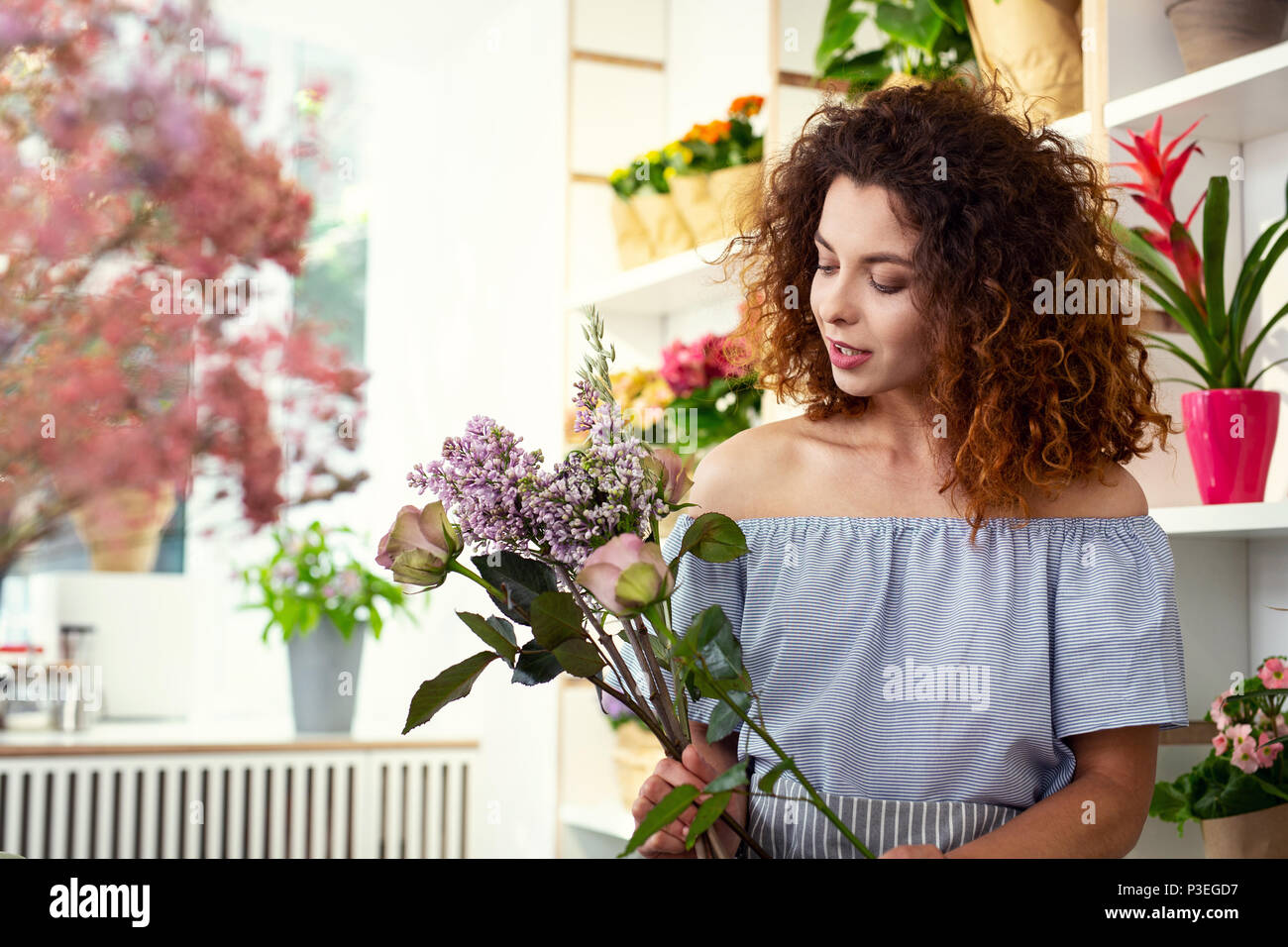 Pleasant creative woman looking at the flowers - Stock Image