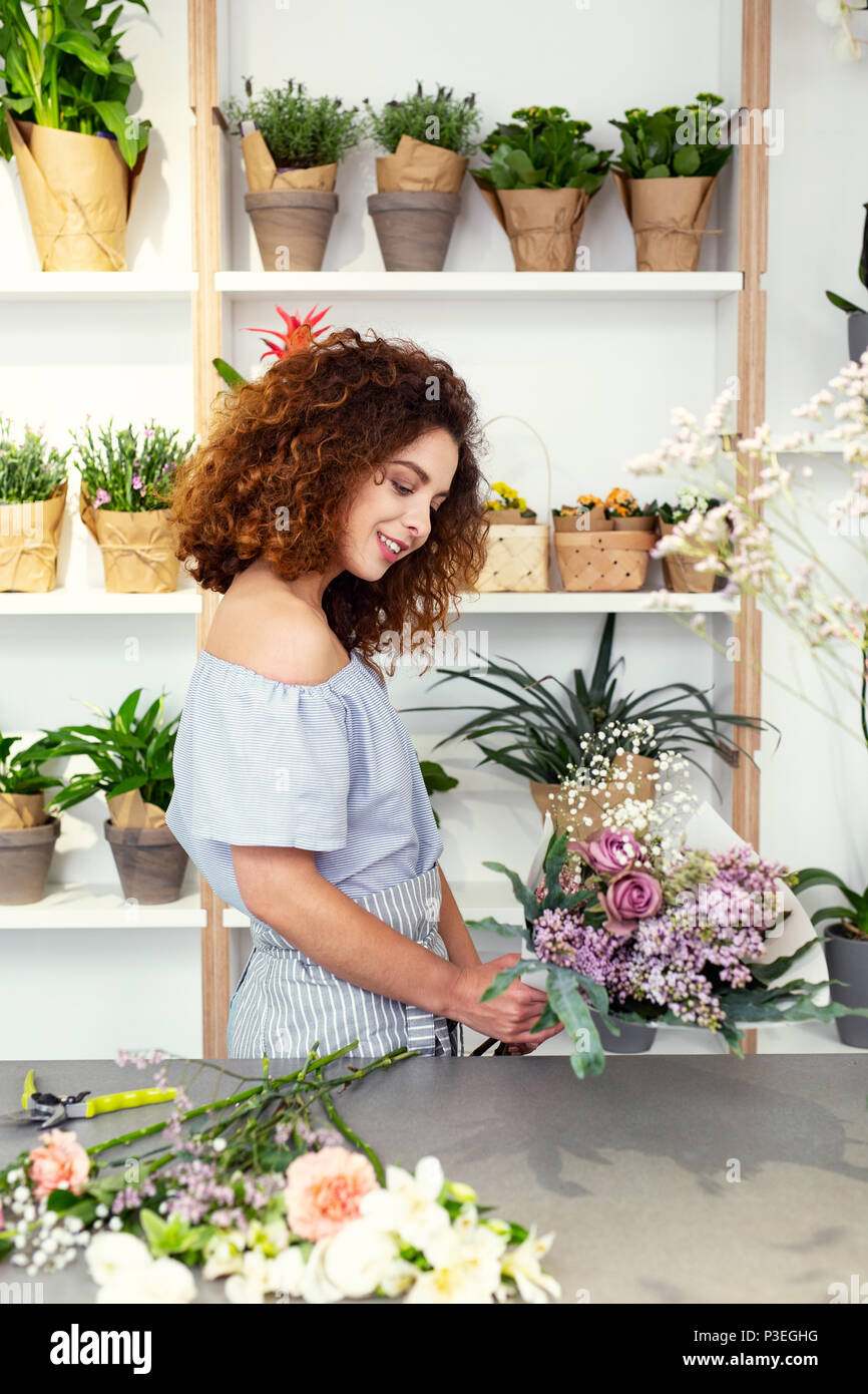 Nice skillful florist enjoying her work - Stock Image