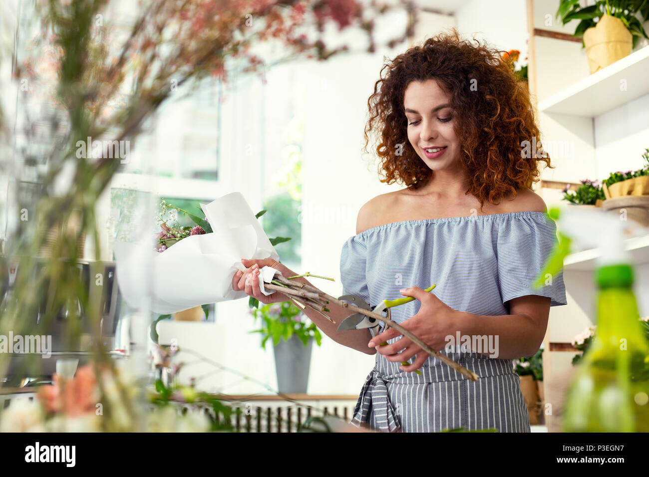 Nice delighted florist looking at the bouquet - Stock Image