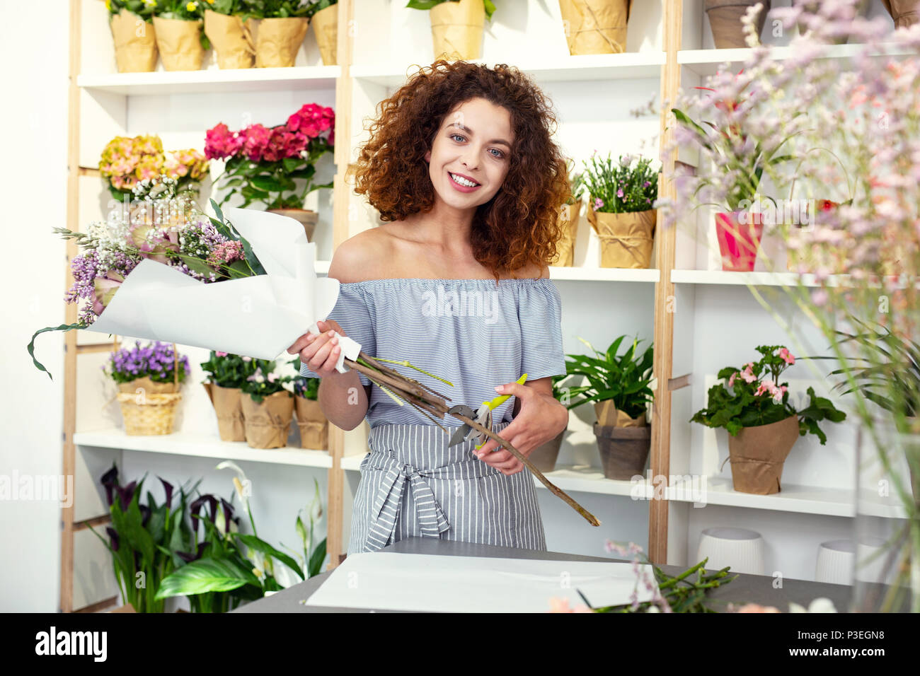Joyful happy florist smiling - Stock Image