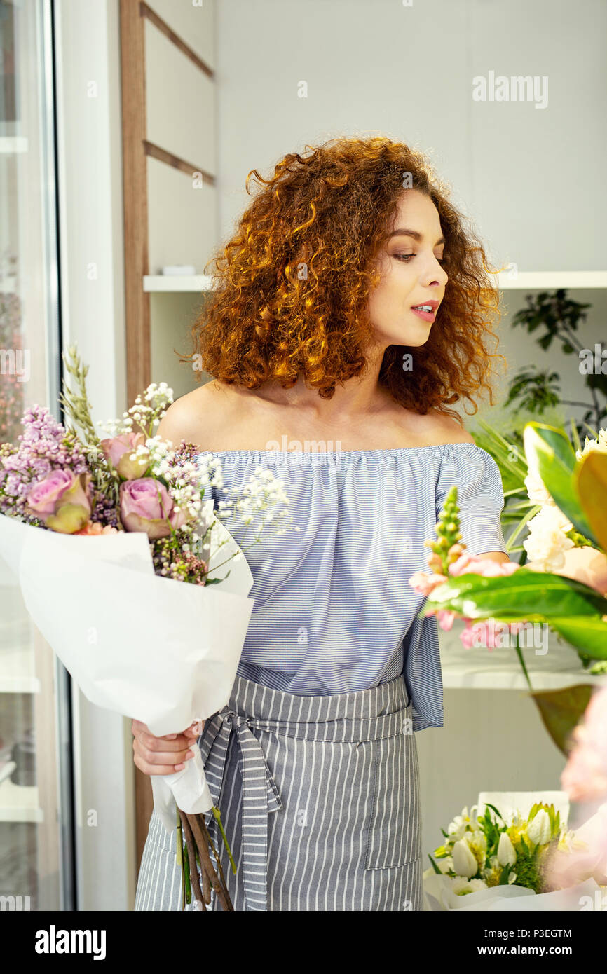 Nice attractive woman working as a florist - Stock Image