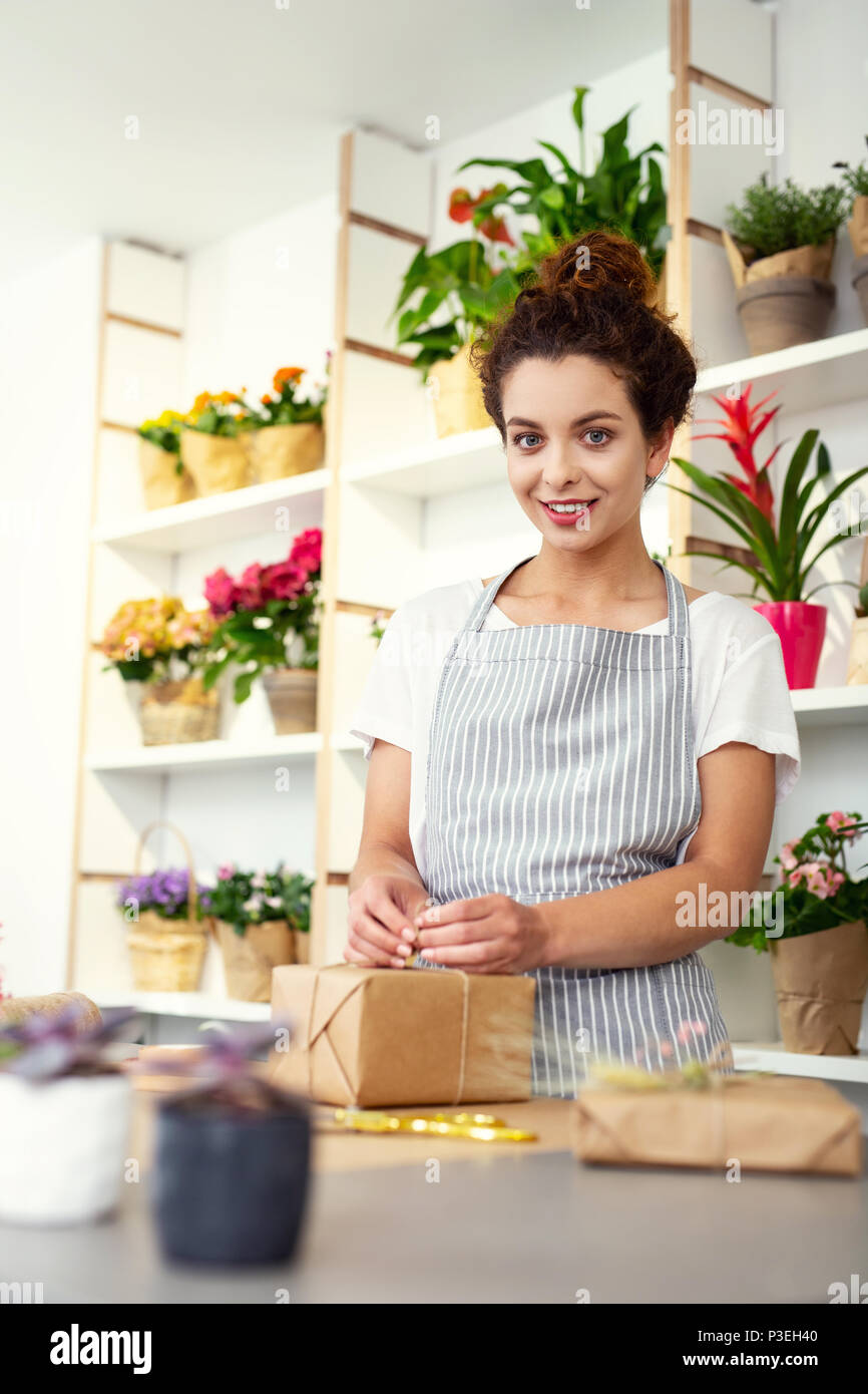 Cheerful happy woman wrapping a gift - Stock Image