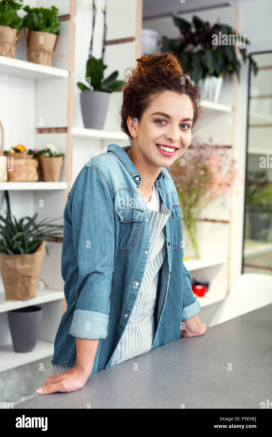 Nice happy woman standing at the counter - Stock Image