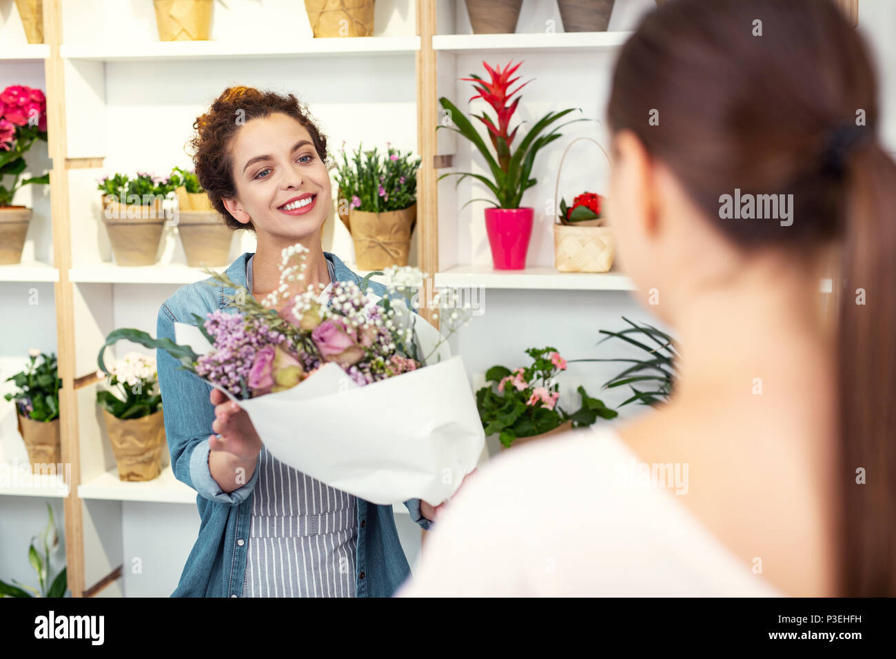 Delighted nice woman offering bouquet - Stock Image