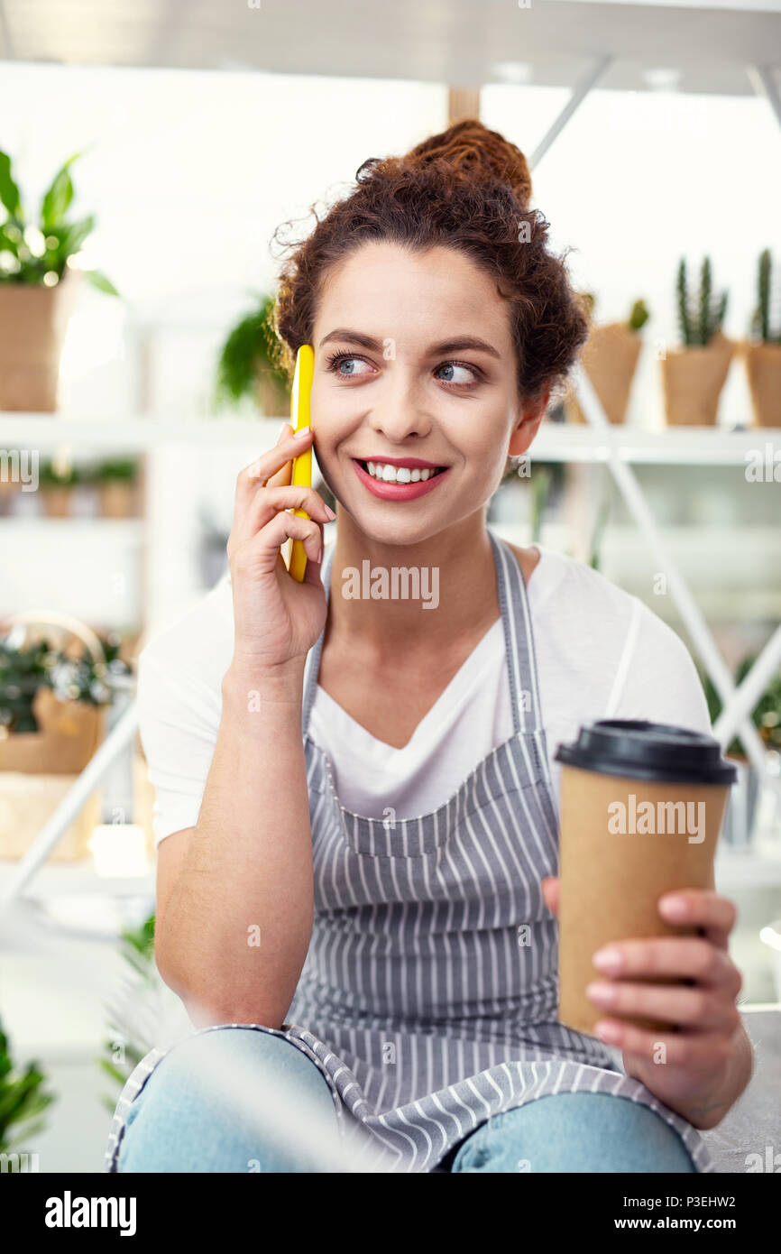 Positive cheerful woman talking on the phone - Stock Image