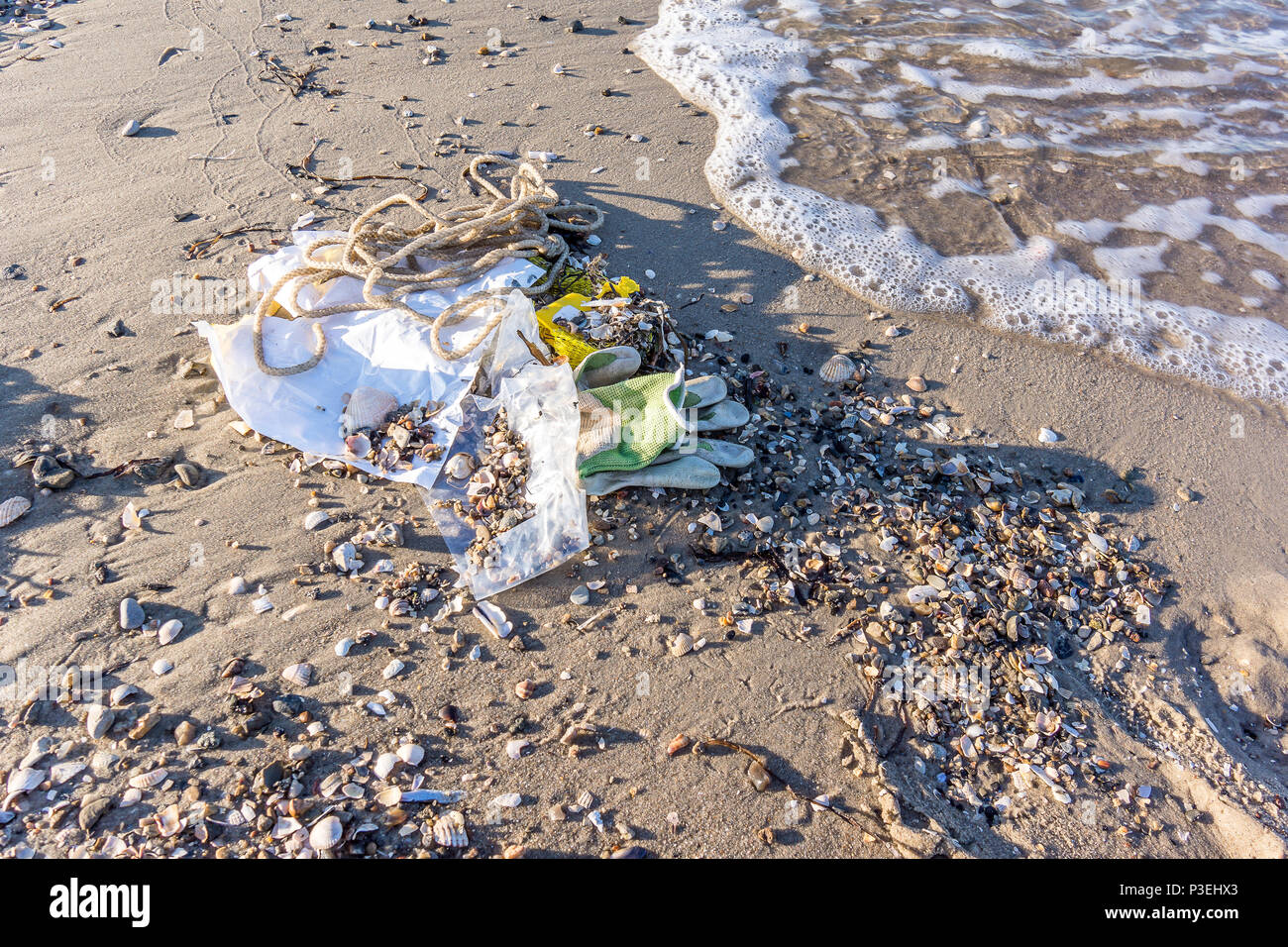 A plastic bottle and other rubbish on the sand, washed by the waves, a closeup of a polluted beach, Vejle, Denmark, June 6, 2018 - Stock Image