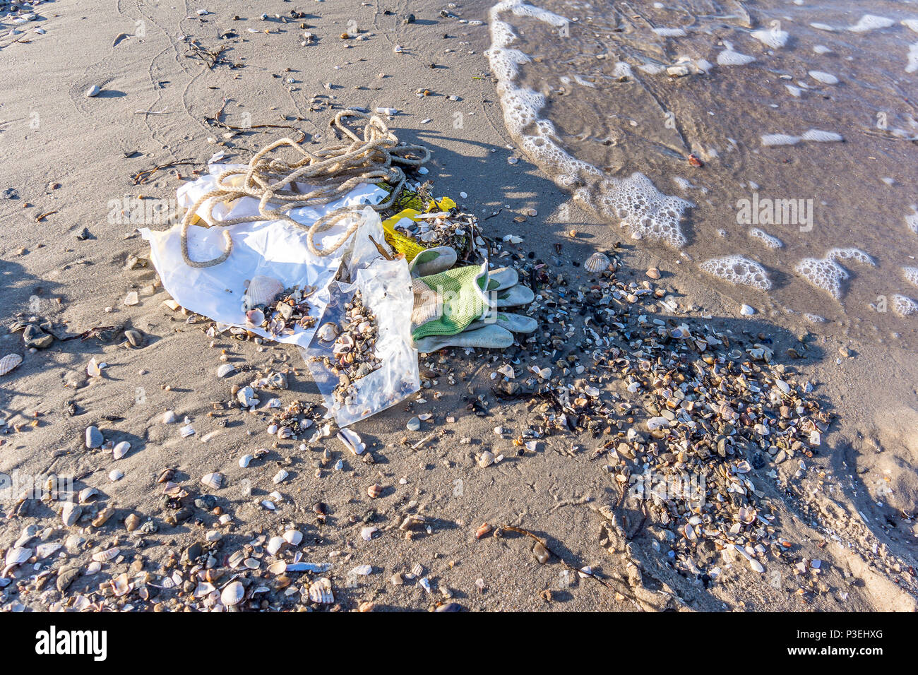 A plastic bottle and other rubbish on the sand close to the sea,  a closeup of a polluted beach, Vejle, Denmark, June 6, 2018 - Stock Image