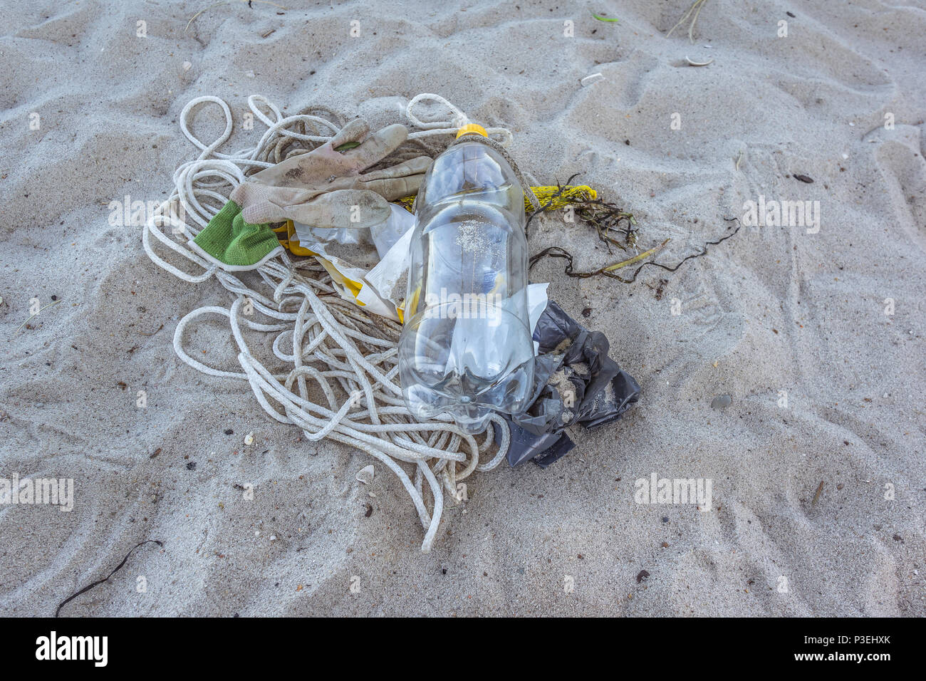 A plastic bottle and other litter on the sand, a closeup of a polluted beach, Vejle, Denmark, June 6, 2018 - Stock Image