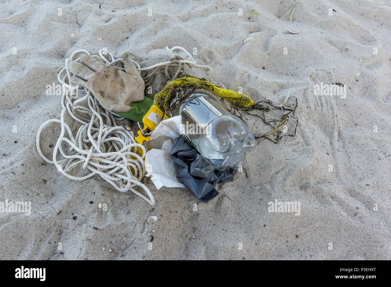 A plastic bottle and other rubbish on the sand, a closeup of a polluted beach, Vejle, Denmark, June 6, 2018 - Stock Image