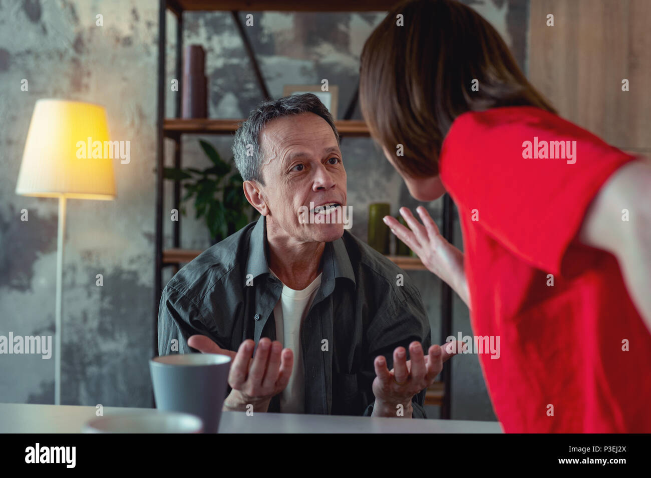 Angry man feeling fierce while shouting at his wife - Stock Image