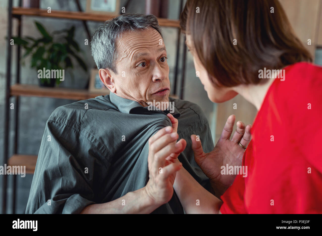 Concerned wife grabbing her husband having dispute - Stock Image