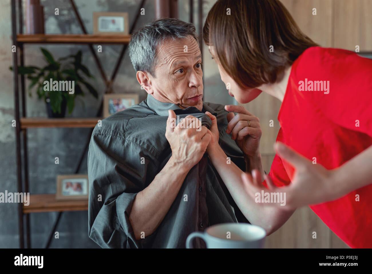 Crazy woman beating her mature husband - Stock Image