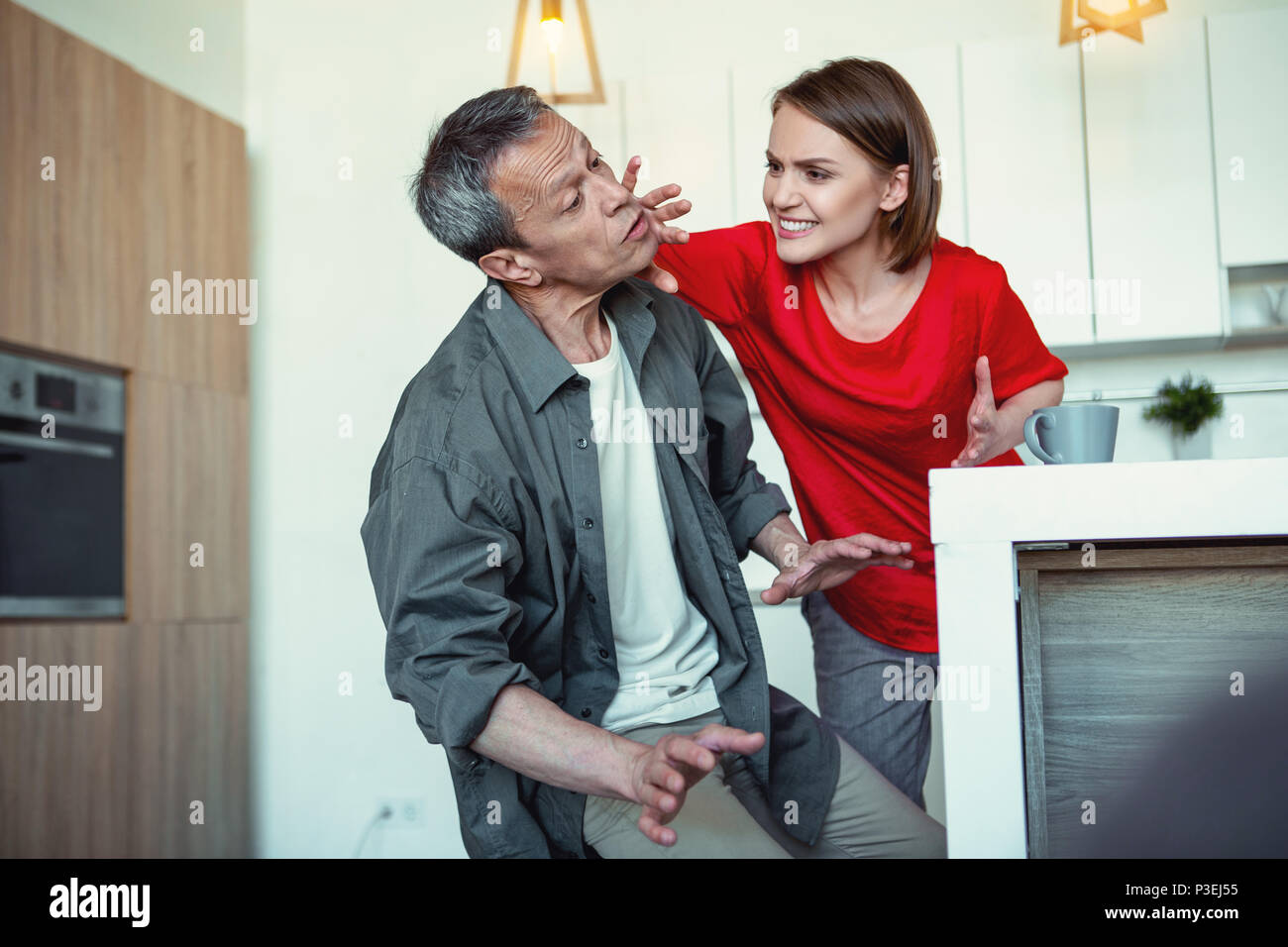 Insane dark-haired woman beating her husband - Stock Image