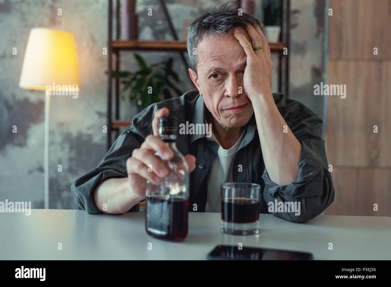 Mature man drinking whisky after divorce - Stock Image