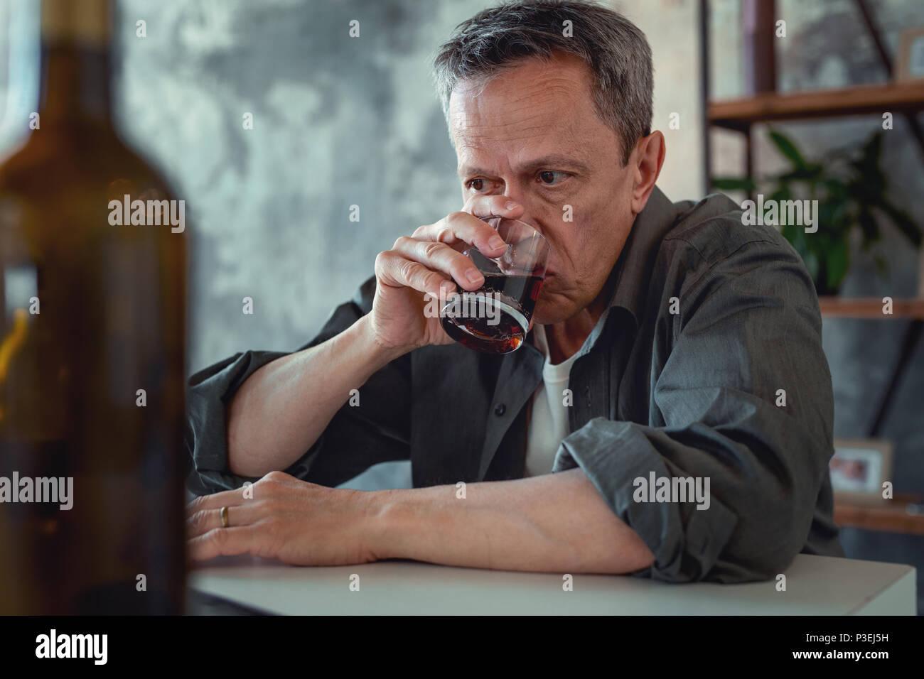 Mature man wearing dark shirt drinking cognac - Stock Image