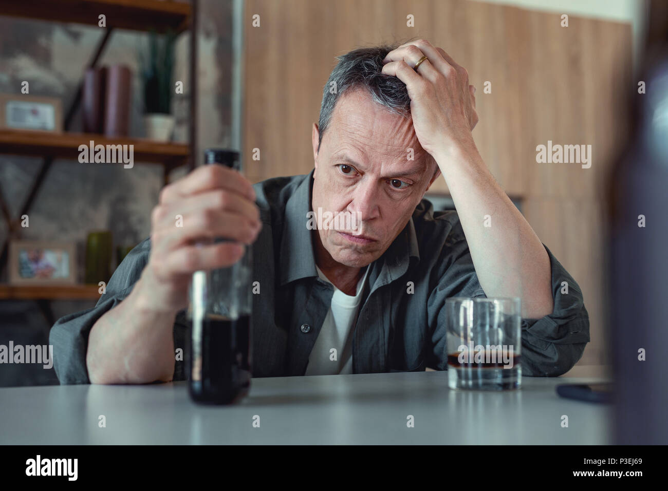 Dark-eyed man looking at the bottle of cognac - Stock Image