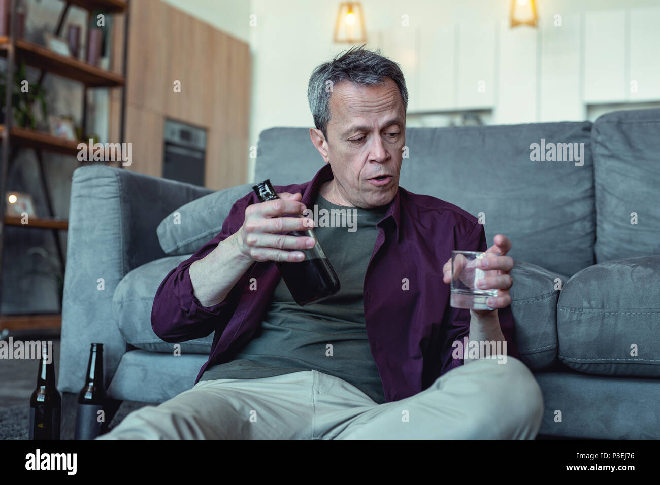 Man with facial wrinkles sitting with glass of vodka - Stock Image