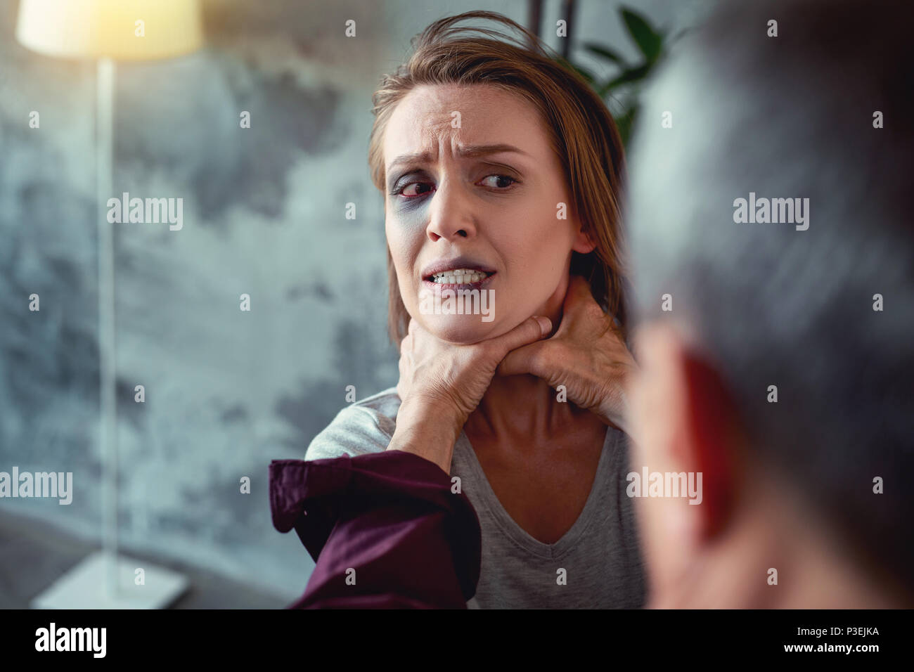 Young woman with blue eye and blood on lip - Stock Image