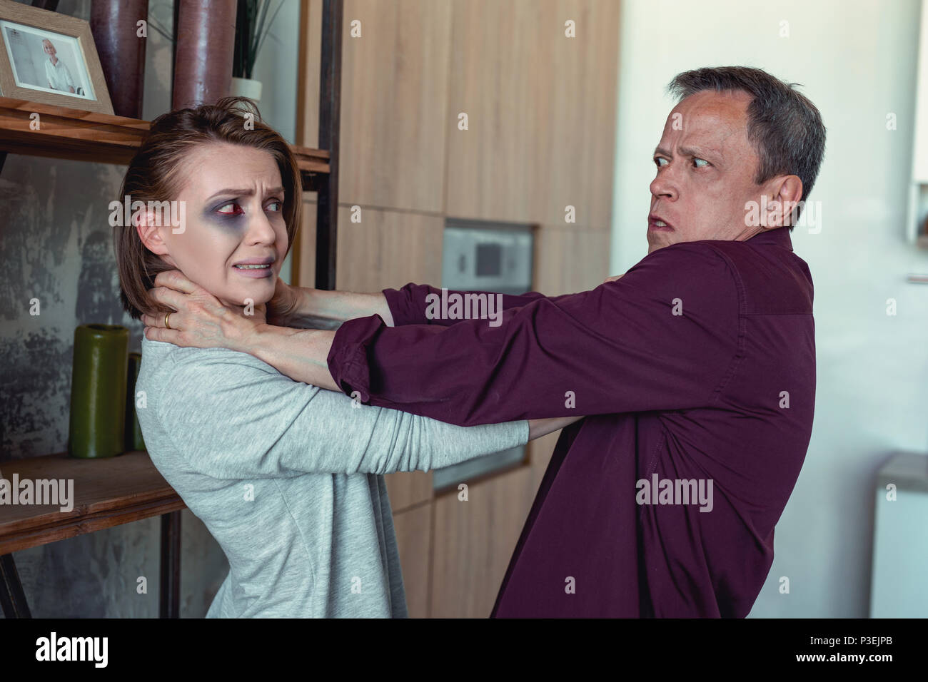 Crazy robber strangling his victim at the place of criminal - Stock Image