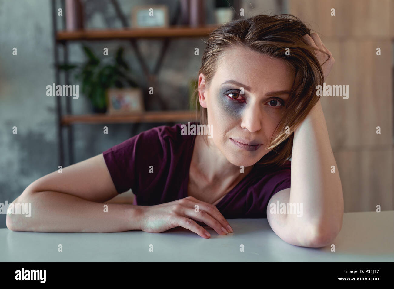 Crying wife having split lip after family dispute - Stock Image